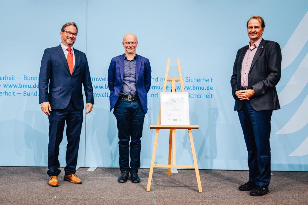 Architekt Christian Kirchberger (Mitte) erhielt den Preis vom Parlamentarischen Staatssekretär Florian Pronold (li.) und dem Leiter des Bundesumweltamts, Prof. Dr. Dirk Messner. Foto: Christoph Wehrer/BMU,